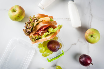 Back to school. A healthy lunch in a box is fresh fruit (apples, plums, grapes), a bottle of yogurt and a sandwich with lettuce, tomatoes, cheese, meat. White marble table. Copy space top view