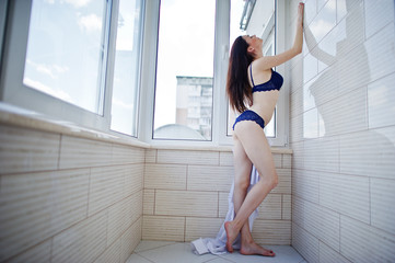 Portrait of an amazing woman in beautiful female underwear and male shirt posing on the balcony.