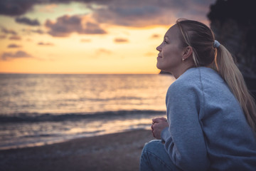 Pensive lonely smiling woman looking with hope into horizon during sunset at beach Wall mural