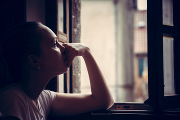 Pensive thoughtful young woman lost in thoughts dreaming and looking in opened  window in vintage style with dramatic mood