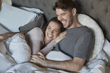 Affectionate mid adult married couple lying in bed together.