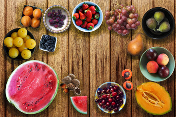 Summer fruits on wooden table. Watermelon, melon, yellow plum, apricot, mulberry, blackberry, strawberry, grape, fig, pear, peach, plum, nectarine, cherry, nut, walnut