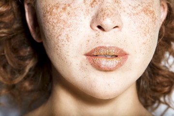Close up of young woman's lips covered with glitter