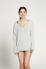 Smiling model wearing grey sweater.