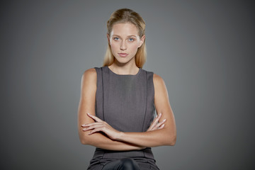 Portrait of young woman with her arms crossed.