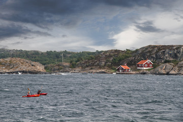 Two persons kayaking in the ocean in the coast of Sweden with typical red houses and small rock hills seen in the background with dark and light clouds on the background.