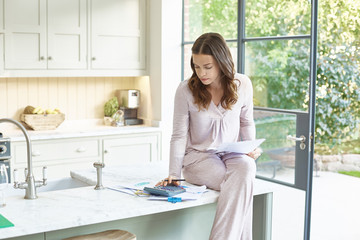 Mid adult woman doing paperwork on kitchen counter.