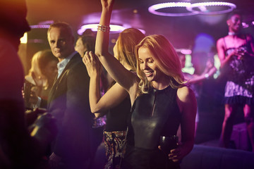 Young woman dancing with friends at nightclub