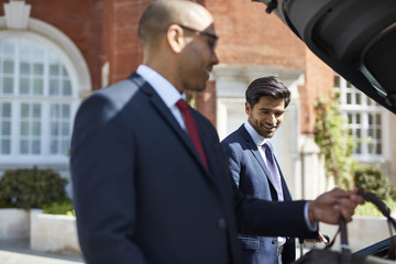 Businessmen unloading luggage from car