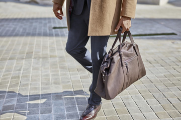 Legs of businessman carrying bag
