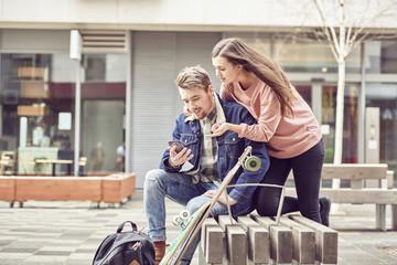Teenage couple using smart phone together