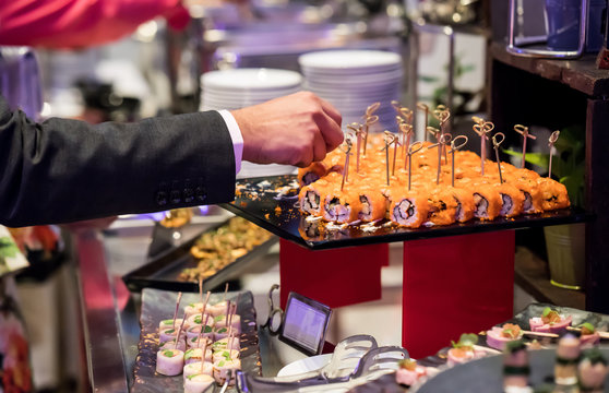 Businessman hands pricking califonia sushi roll in cocktail buffet