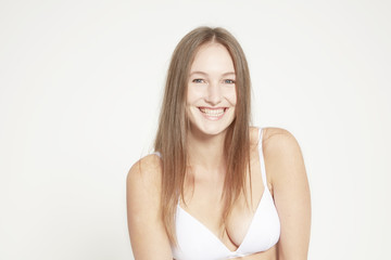 Smiling model wearing white bra.