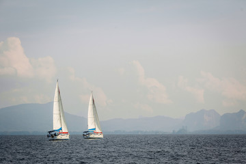 Two yacht floats sails along the rocky shore. Beautiful scenery of sailing