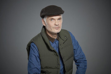Portrait of mature man wearing vest and flat cap.