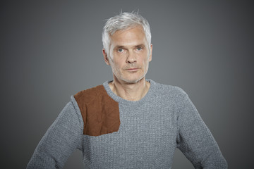 Portrait of mature man wearing gray sweater.