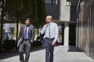 Businessmen walking along sidewalk together