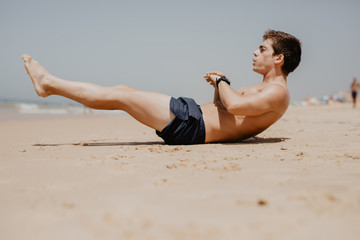 Side view portrait of a young man exercising on the beach doing sit ups