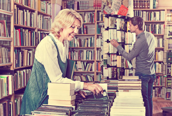 Mature smiling woman picking new book
