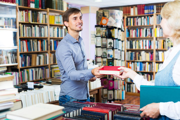 Man taking book from seller