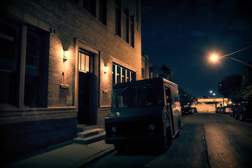 Wall Mural - An armed security truck parked in a dark city street at night next to a building entrance.