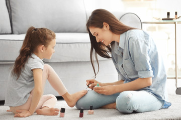 Young woman and her little daughter doing pedicure at home