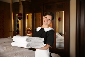 Chambermaid holding clean towels in hotel room