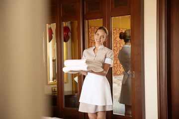 Chambermaid holding clean white folded towels in hotel room