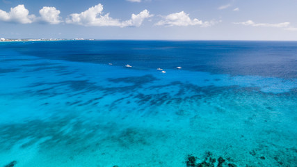 Dive boats over a large shipwreck in clear, blue, tropical waters