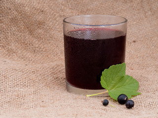 Blackcurrant juice in glass. Hessian behind.