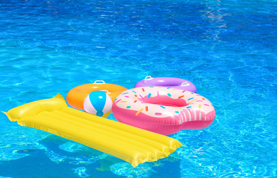 Inflatable rings, mattress and ball in blue swimming pool