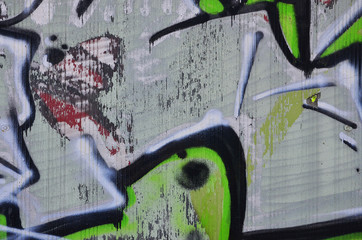 Close up view of graffiti drawing details. Background image on the theme of street art and vandalism. Texture of the wall, painted with aerosol paints