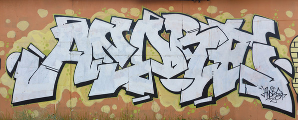 A photograph of a detailed wall artwork. Graffiti drawing is made with white paint with black outlines and has a monophonic orange background. Texture of wall with graffiti decoration