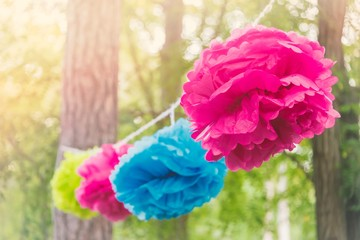 Close up of a colorful party garland made of paper flowers tied between trees in a park at an open air celebration event.