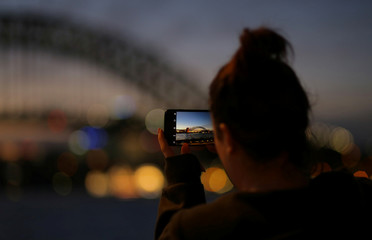 The Sydney Harbour Bridge is photographed on a mobile phone after sunset in Sydney, Australia