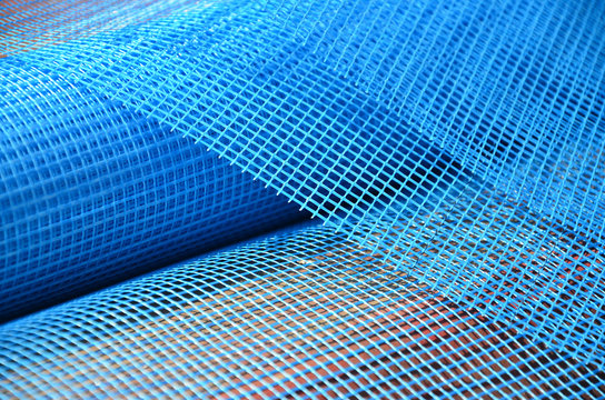 Close-up texture of a blue reinforcing mesh rolled up in a roll. Building resource for reinforcing walls in the process of their warming