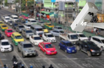 CCTV Security camera monitoring on street. Blurred traffic background.