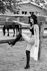 Woman on a rancho near horses farm posing at camera and have fun, girl in american country style