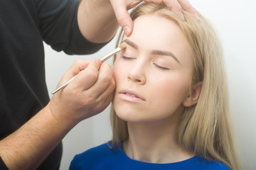 Hands applying concealer on girl eyelids with makeup brush