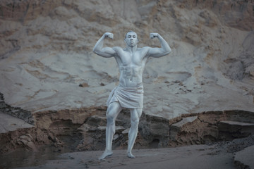 Statue of a bodybuilder man posing showing off his body.