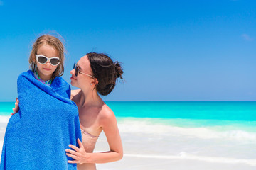 Happy mother and little girl on the beach vacation. Little girl in towel on the seashore