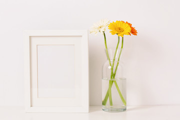 Empty frame mockup for design presentation and bouquet of flowers on a white wall background. Romantic minimalism design.