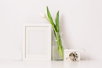 Mock up of blank photo frame with flower and paper film camera