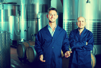 Two cheerful winery employees standing on winery