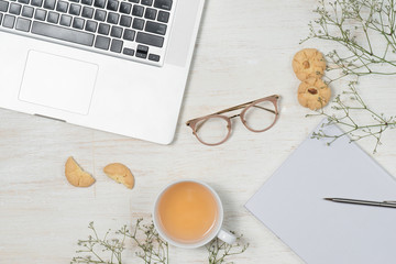 Top view of working desk with blank notebook with pen, coffee cup, mobile phone and cookies on wooden background