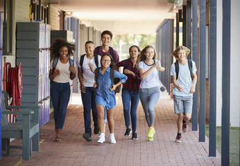 Teenager school kids running in high school hallway