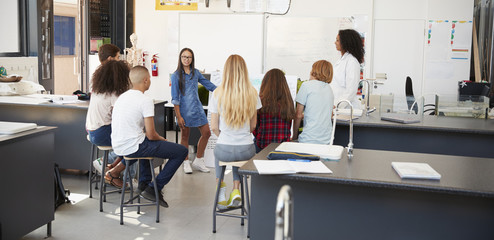 Schoolgirl presenting project in front of science class
