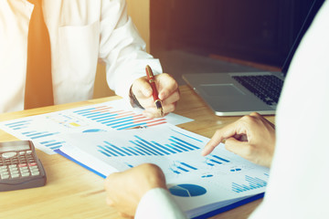 Business analyze concept with two businessman looking summary report on paperwork and laptop on desk for searching data result.