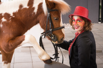Young beautiful lady artist with shiny top hat and her pony