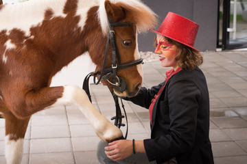 Lady artist with red top hat and tuxedo with her pony